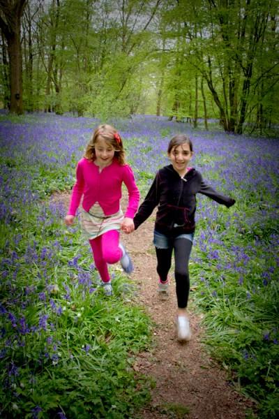 children running with bluebells